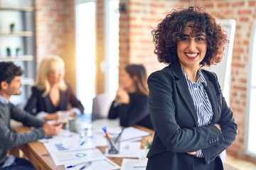 Group of business workers working together. Young beautiful woman standing smiling happy looking at the camera at the office
