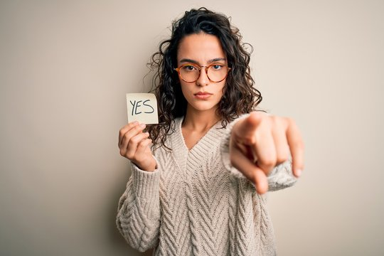 Young beautiful woman with curly hair holding reminder paper with yes word message pointing with finger to the camera and to you, hand sign, positive and confident gesture from the front