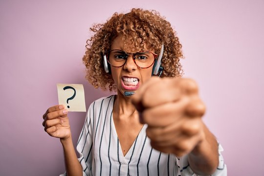 African american call center agent woman using headset holding paper with question mark annoyed and frustrated shouting with anger, crazy and yelling with raised hand, anger concept