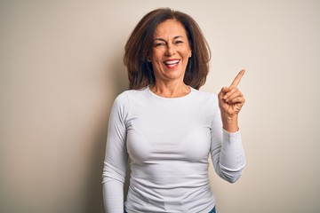 Middle age beautiful woman wearing casual t-shirt standing over isolated white background with a big smile on face, pointing with hand and finger to the side looking at the camera.