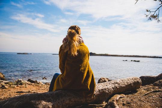 Femme seule de dos regardant la mer