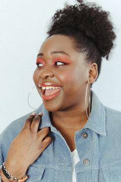 portrait of young black woman wearing orange eye make-up and blue jacket looking sideways and smiling