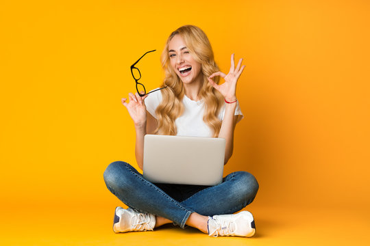 It's okay. Overjoyed woman showing ok sign, sitting with laptop