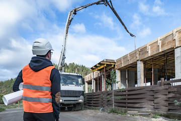 A man watches the pouring of concrete on a construction site. Construction of a country house. A person controls the pouring of concrete. Housing construction. A cement mixer pours cement.