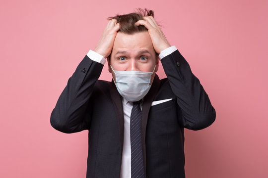 Young caucasian man in a medical mask os being stressed with coronavirus pandemic