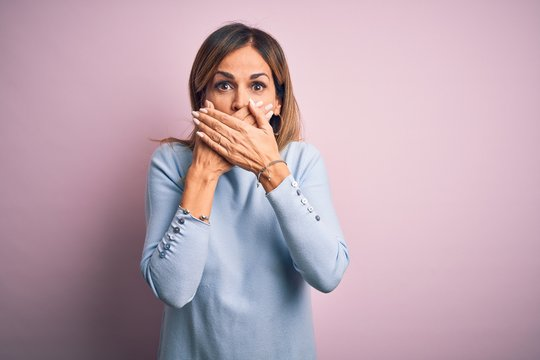 Middle age beautiful woman wearing casual t-shirt standing over isolated pink background shocked covering mouth with hands for mistake. Secret concept.