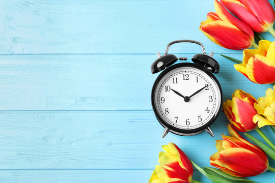 Black alarm clock with spring flowers and space for text on light blue wooden background, flat lay. Time change