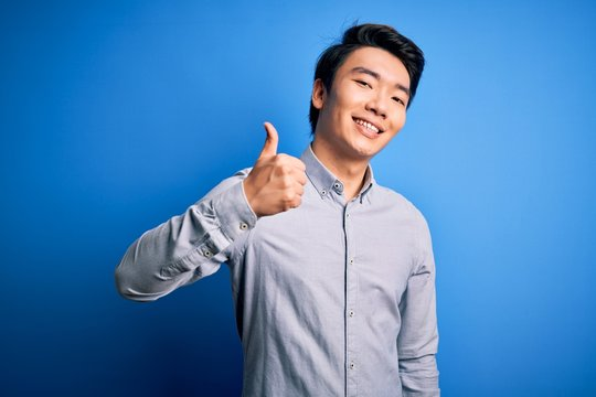 Young handsome chinese man wearing casual shirt standing over isolated blue background doing happy thumbs up gesture with hand. Approving expression looking at the camera showing success.