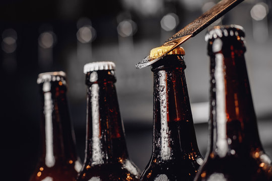Row brown ice cold beer bottle with water drops and metal opener cap, dark background