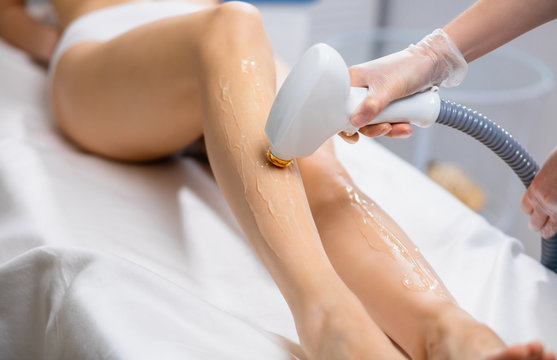 close-up of young caucasian slender woman getting laser epilation in beauty salon. hair removal from legs with the use of special apparatus