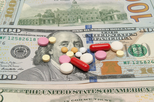 Various pills are on the background of a 100 dollar bill.