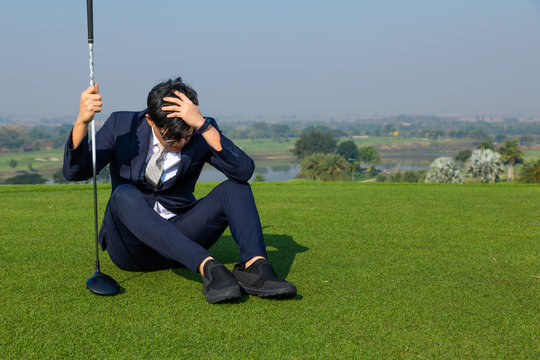 Frustrated stressed  Business man wearing suits it sad about losing on the golf course. Portrait of Asian businessman suffering from a headache