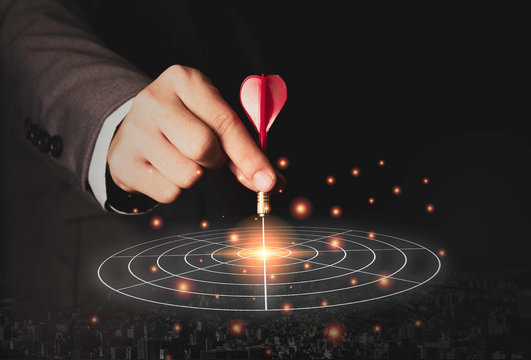 Executive marketing hand holding red dart put to centre of target board. Business investment goal and target concept.