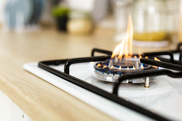 Macro closeup of modern luxury gas stove top with blue fire flame knobs bokeh blurry blurred background