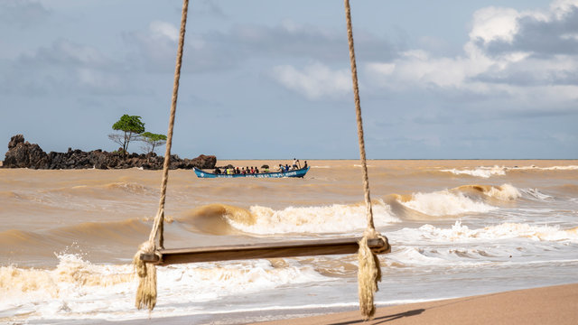 A hanging swing on an empty beach with a fishing boat in the background on the way out and the fishing spot is Axim Ghana West Africa.