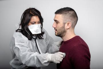 medico con maschera e tuta di protezione visita un paziente con stetoscopioo