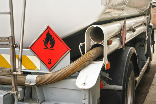 Red Warning hazmat Flammable class 3 liquid sign on back of fuel truck at petrol station