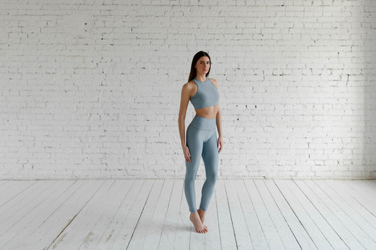 A girl in a sports top and leggings stands against a white brick wall