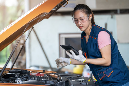 Girl engineer mechanics working on a vehicle in a garage or service workshop