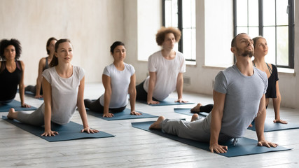Male instructor and group of people performing Upward Facing Dog