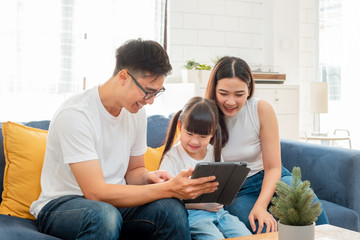 Happy Asian family using tablet, laptop, phone for playing game watching movies, relaxing at home for technology lifestyle concept