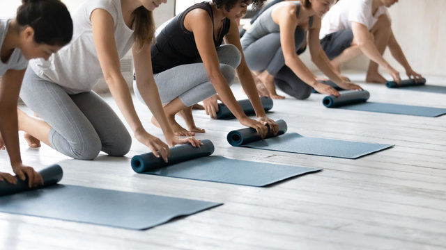 Multiethnic people folding mats finished yoga session at sport club