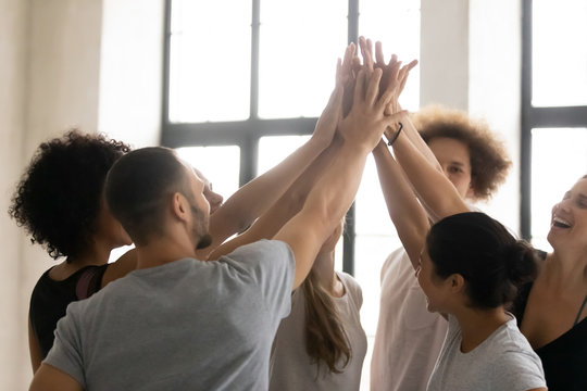 Multiethnic sportive people stacked palms together celebrating sport victory