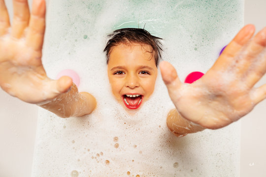 Cute boy with smile laugh and happy scream swim on the back in soap at home bath reaching up hand