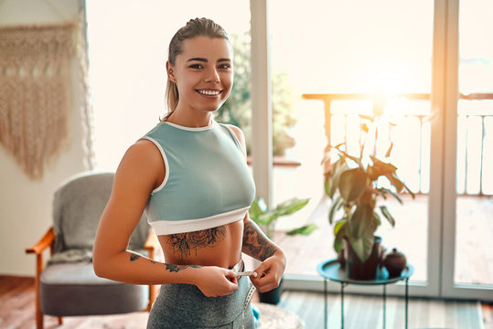 Weight loss, slim body, healthy lifestyle concept. Slim young woman measuring her thin waist with a tape measure at home in the living room.