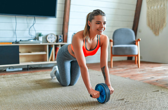 Beautiful strong woman in sportswear is working out with exercise wheel at home in the living room. Sport and recreation concept.