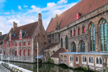 Foto auf Leinwand Brugge Bruges, Belgium old houses and a cathedral on a canal near a wooden pier