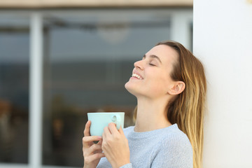 Happy woman relaxing in a terrace holding coffee mug