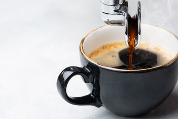 Fresh hot coffee is poured into a Cup from the coffee machine