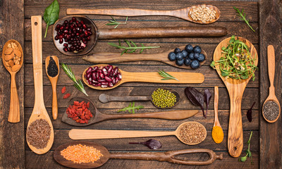 Various superfoods set in wooden spoons pomegranate seeds, almond, blueberries, sesame, goji, mung bean turmeric and lentils. Vegetarian healthy eating diet organic products  clean eating concept.