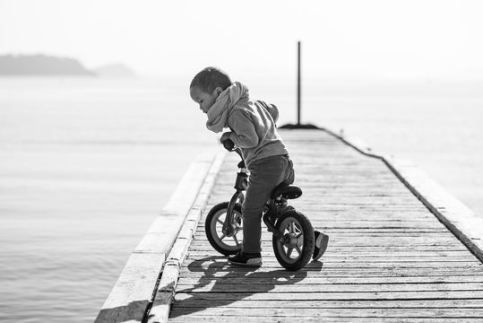 Jeune enfant en draisienne regardant la mer