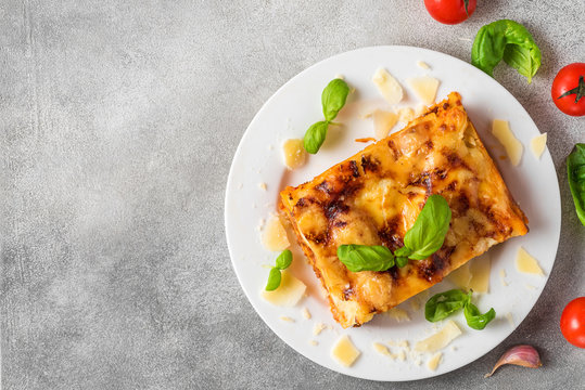Meat lasagna with fresh basil and parmesan cheese in a plate on gray concrete background. top view with copy space