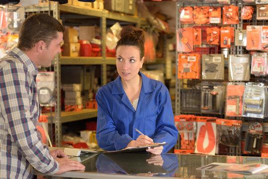 shop assistant serving customer at counter of motorfactors
