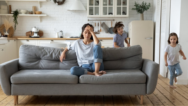 Exhausted young mother annoyed from loud children