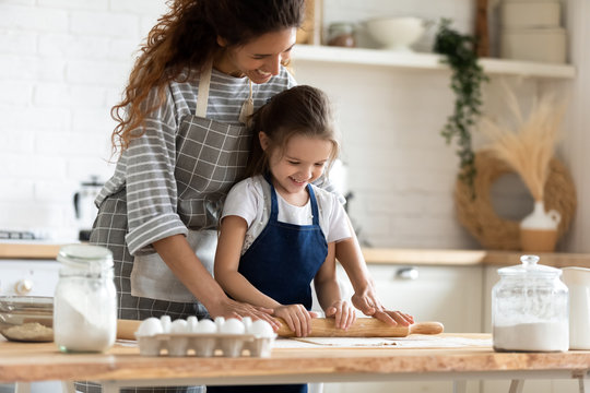 Young mom and little daughter baking in kitchen together