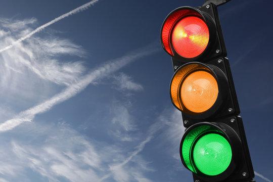 Semaforo rosso, giallo e verde con il cielo come sfondo