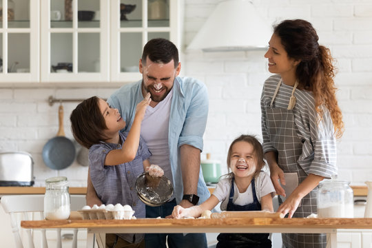 Overjoyed parents with little kids have fun cooking in kitchen