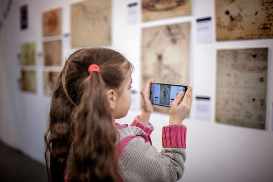 Curious girl exploring a contemporary art exhibition with augmented reality mobile application