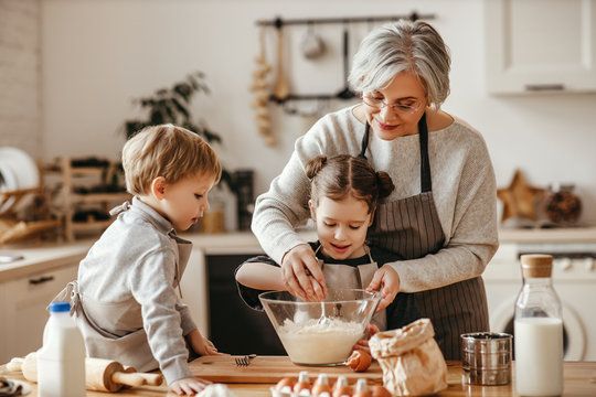 happy family grandmother and grandchildren cook in the kitchen, knead dough, bake cookies.