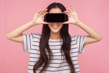 Anonymous mobile user. Portrait of girl with long brunette hair in striped t-shirt hiding eyes with cell phone and smiling, unknown internet customer. indoor studio shot isolated on pink background