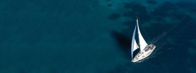 Fototapeta Aerial drone ultra wide photo of beautiful sail boat sailing in tropical exotic bay with emerald clear sea