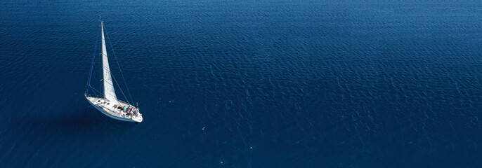 Aerial drone ultra wide photo of beautiful sail boat cruising in Aegean deep blue sea