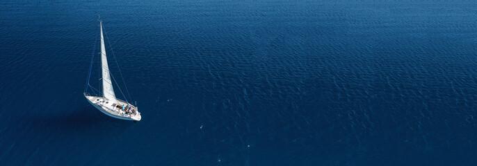 Aerial drone ultra wide photo of beautiful sail boat cruising in Aegean deep blue sea