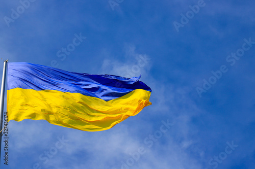 The big national flag of Ukraine flies in the blue sky. Big yellow blue Ukrainian state banner in the city of Dnipro, Dnipropetrovsk. Independence, Constitution Day, National Day, text space