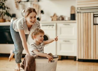 Happy family mother housewife and child   in laundry with washing machine . Wall mural