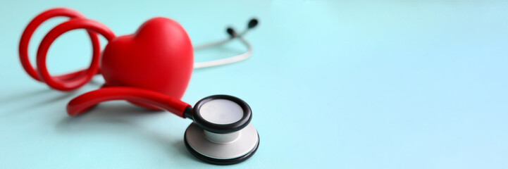 Red stethoscope with heart on blue modern background. Medical insurance concept Wall mural
